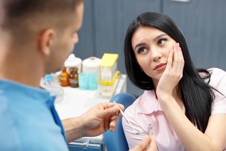 Chica paciente va al dentista con un dolor de muelas en el consultorio dental. Mujer joven que sostiene la mano de un diente enfermo Foto de archivo - 54862244