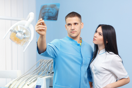 Male dentist and female assistant looking at x-ray picture in the dental office. People, medicine, stomatology and health care concept Stock Photo