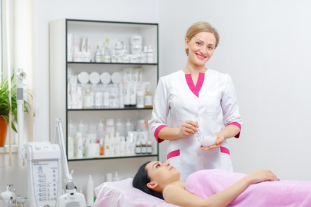 medical therapy: Young woman beautician is doing the cleaning procedure in the beauty salon. Face Skin Care. Cleansing Procedure. Cosmetology.