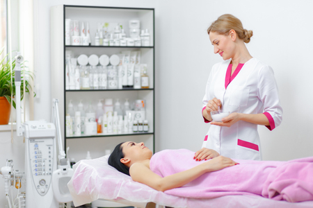 Junge Frau Kosmetikerin tut, um die Reinigungsprozedur in der Schönheitssalon. Gesichtspflege. Reinigungsverfahren. Kosmetologie. Standard-Bild - 54862590