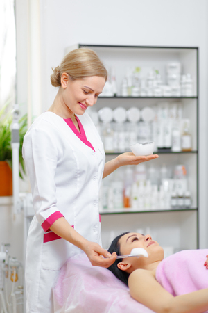 resurfacing: Young woman beautician is doing the cleaning procedure in the beauty salon. Face Skin Care. Cleansing Procedure. Cosmetology.