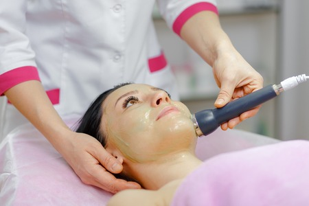 rf: Face Skin Care. Young beautiful woman with dark hair gets procedure in the beauty salon.  Ultrasound Cavitation anti-aging, Rejuvenation, Lifting Procedure. Beauty Concept