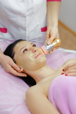 electrophoresis: Face Skin Care. Young beautiful woman with dark hair gets procedure in the beauty salon.  Ultrasound Cavitation anti-aging, Rejuvenation, Lifting Procedure. Beauty Concept