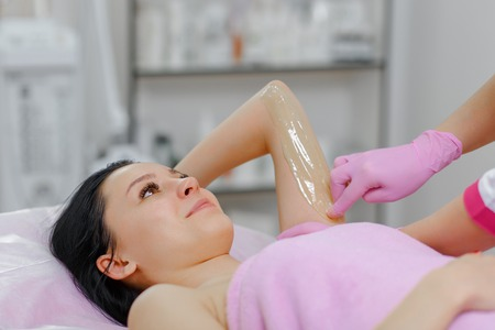 sugaring: Sugaring: Beauty Concept. Young beautiful girl with dark hair gets the procedure for hair removal liquid sugar