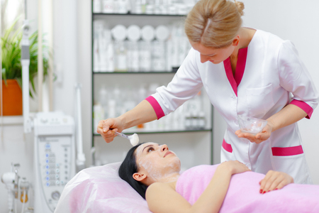 gets: Young beautiful woman with dark hair gets procedure in the beauty salon. Face Skin Care. Cleansing Procedure. Cosmetology.