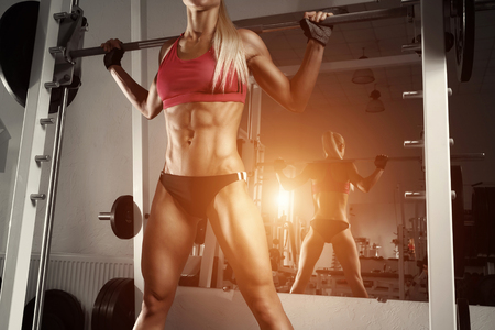 Fitness woman doing squats with the barbell at the gym. Smith Machine in the gym.  Fitness woman in the gym. Perfect female figure Stock Photo