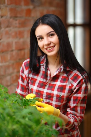 joyfully: Growing perfect. Stunning young woman doing some gardening smiling joyfully looking to the camera.