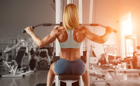 Blonde sexy fitness girl in sport wear with perfect body in the gym posing before training set. Attractive fitness woman, trained female body