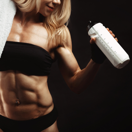 white towel: Strong muscular woman with a shaker and white towel on the black background