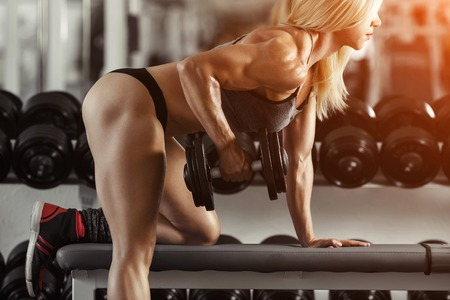 Classic bodybuilding. Muscular blonde woman doing exercises in the gym Stock Photo