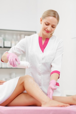 sugaring: Woman beautician prepares the skin for legs Hair removal. Sugaring: Beauty Concept. Skin Care. Hair removal Procedure. Cosmetology. Cosmetology salon
