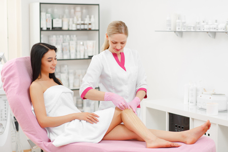 sugaring: Sugaring: Beauty Concept. Hair removal on legs. Young beautiful girl with dark hair gets the procedure for hair removal liquid sugar. Beautician Giving Epilation To Woman On Thigh