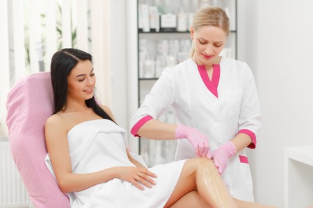 Sugaring: Beauty Concept. Hair removal on legs. Young beautiful girl with dark hair gets the procedure for hair removal liquid sugar. Beautician Giving Epilation To Woman On Thigh