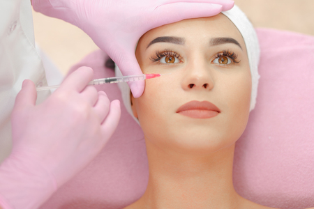 aging woman: Woman gets injection in her face. Beauty woman giving botox injections. Young woman gets beauty facial injections in the cosmetology salon. Face aging injection. Aesthetic Medicine, Cosmetology