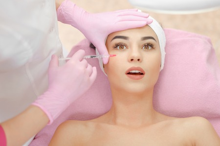 medical injection: Woman gets injection in her face. Beauty woman giving botox injections. Young woman gets beauty facial injections in the cosmetology salon. Face aging injection. Aesthetic Medicine, Cosmetology