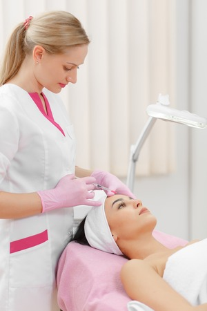 aging face: Woman gets injection in her face. Beauty woman giving botox injections. Young woman gets beauty facial injections in the cosmetology salon. Face aging injection. Aesthetic Medicine, Cosmetology