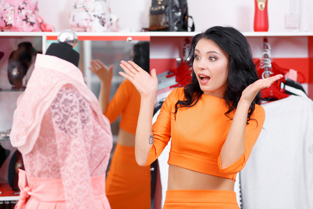 admires: Young woman admires the dress. Woman shopping for dress in clothing retail store. Caucasian shopper girl choosing pink dress in shop during sale. Woman shopping for dress. Fashion shopping