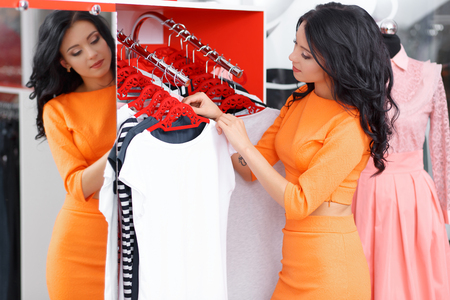 outrage: Young woman buys a white T-shirt. Woman shopping for dress in clothing retail store. Caucasian shopper girl in shop during sale. Woman shopping for dress. Fashion shopping