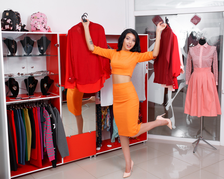 outrage: Young woman shopping in a clothing store. Woman shopping for dress in clothing retail store. Caucasian shopper girl choosing red dress in shop during sale. Woman shopping for dress. Fashion shopping