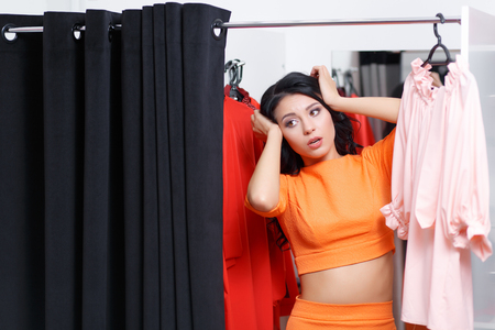 fitting room: Young woman astonished in a fitting room looking at the camera. Fashionable woman shopping in a clothing store. Woman shopper in a fitting room. Woman shopping for dress. Woman shopaholic. Shopping