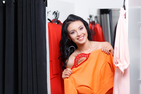 fitting room: Can you bring me on more dress please. Fashionable young woman shopping in a clothing store. Woman shopper in a fitting room. Woman shopping for dress. Woman shopaholic. Fashion shopping