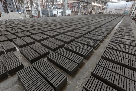 specific: Stack of bricks. Manufacturing of aerated concrete blocks. Manufacturing of cinder block. The plant manufactures building material. The plant produces a cinder block. Cinder block-building material.