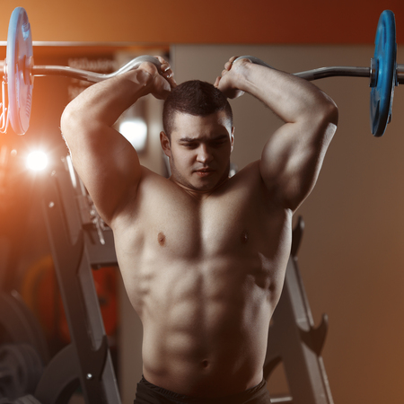 Fitness man exercising with barbell in gym. Fitness man deadlift barbell in the gym. Fitness man in the gym. Sports and fitness - concept of healthy lifestyle. Stock Photo
