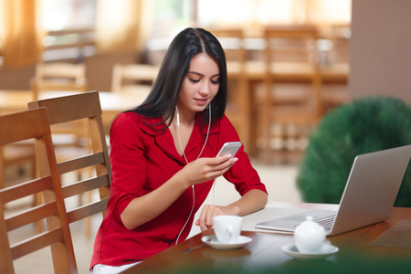 Young businesswoman using phone in coffee shop. Successful businesswoman. Young woman with phone and laptop sitting in the cafe. Attractive woman reading text message on cell telephone in cafe.