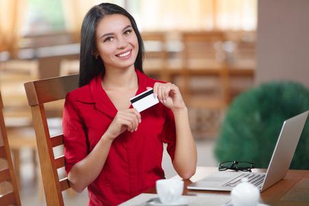 De creditcard van de bedrijfsvrouwenholding en het bekijken de camera. Zakenvrouw online winkelen. Zakenvrouw betaalt voor een aankoop met een creditcard. Kopen op internet. Koop online. Online winkelen Stockfoto