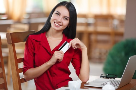 Business woman holding credit card and looking at the camera. Business woman shopping online. Business woman pays for a purchase with credit card. Purchase on the Internet. Buy online. Shopping online Banco de Imagens - 61565011