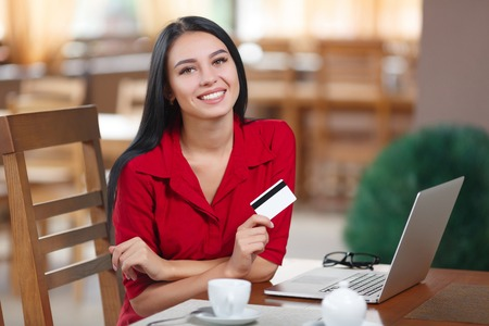 Business woman holding credit card and looking at the camera. Business woman shopping online. Business woman pays for a purchase with credit card. Purchase on the Internet. Buy online. Shopping online