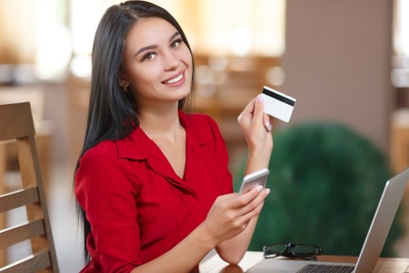 Young business woman holding mobile phone and credit card. Woman pays for a purchase with credit card. Purchase online. Shopping online Imagens