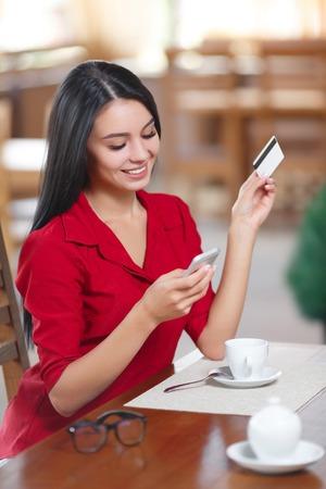 Mujer de negocios joven que sostiene el teléfono móvil y la tarjeta de crédito. La mujer paga por una compra con tarjeta de crédito. Compra en línea. Compra en línea Foto de archivo - 61565436