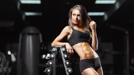 Fitness woman posing in the gym. Perfect physique athletic young woman with six pack, perfect abs, shoulders and biceps.