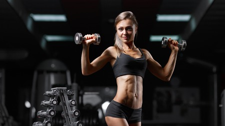 motivator: Fitness woman pumping up muscles with dumbbells. Fitness woman in the gym. Perfect physique athletic young woman with six pack, perfect abs, shoulders and biceps.