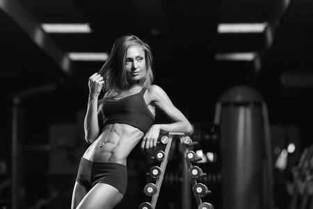 Black and white photo. Fitness woman posing in the gym. Perfect physique athletic young woman with six pack, perfect abs, shoulders and biceps. Stock Photo