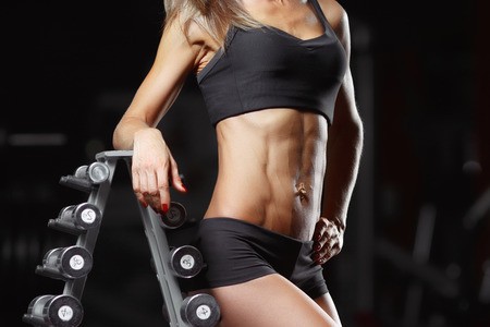 motivator: Fitness woman posing in the gym. Perfect physique athletic young woman with six pack, perfect abs, shoulders and biceps.