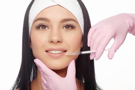 acido: La mujer joven consigue una inyección de botox en los labios. Mujer Primer plano inyección de ácido hialurónico en los labios. Las inyecciones de rejuvenecimiento de la piel. Cosmética procedimientos, inyecciones, botox y ácido hialurónico. Foto de archivo