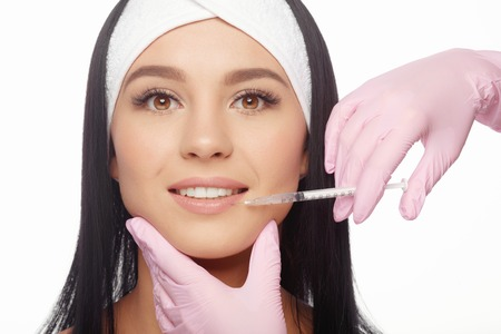 lift hands: Young woman gets a botox injection in her lips. Close-up woman hyaluronic acid injection in lips. Injections of skin rejuvenation. Cosmetic procedures, injections, botox and hyaluronic acid.