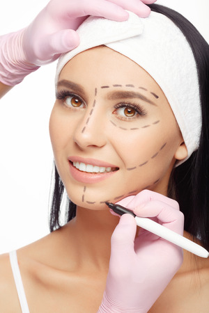 correction lines: Young woman with perforation lines on her face before plastic surgery operation. Beautician touch and draw correction lines on woman face. Isolated