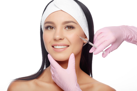 Beautiful woman getting lifting injection in cheekbones. Close-up woman hyaluronic acid injection. Injections of skin rejuvenation. Cosmetic procedures, injections, hyaluronic acid. Banco de Imagens - 63480259