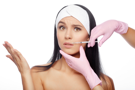 Frightened young woman gets injection in her lips. Close-up woman hyaluronic acid injection in lips. Injections of skin rejuvenation. Cosmetic procedures, injections, hyaluronic acid.