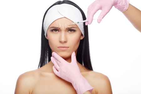 cheekbones: Astonished woman getting lifting injection in cheekbones. Close-up woman hyaluronic acid injection. Injections of skin rejuvenation. Cosmetic procedures, injections, hyaluronic acid. Stock Photo