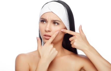 pubertad: La mujer joven apretando su espinilla, la eliminación de la espinilla de la cara. Mujer del concepto del cuidado de la piel. chica lugar espinilla punto de cuidado de la piel cuidado de la belleza del acné en la cara presionando problema de la piel. Foto de archivo