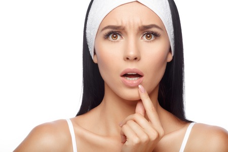 Shocked young woman touching pain her lips. Inflammation of the lip. Woman Skin Care Concept Standard-Bild