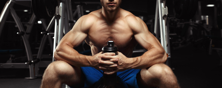 motivator: Young muscular guy sitting with a bottle of water in the gym. Bodybuilder man with a shaker. Muscular Man Resting After Exercise And Hold From Shaker. Sports and fitness. Fitness man in the gym.