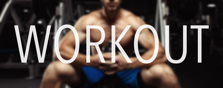 motivator: The word WORKOUT in the blurry background bodybuilder in the gym. Workout word Stock Photo