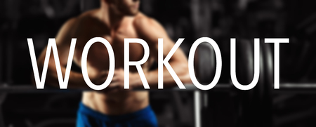 The word WORKOUT in the blurry background bodybuilder in the gym. Workout word Stock Photo