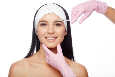 Mujer hermosa que consigue levantar la inyección en la frente. Primer plano de la mujer inyección de ácido hialurónico. Las inyecciones de rejuvenecimiento de la piel. Los procedimientos cosméticos, preparaciones inyectables, ácido hialurónico. Foto de archivo - 63480396