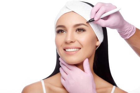 Young woman before plastic surgery operation. Beautiful woman ready for cosmetic surgery, female face with doctors hands with pencil, over white. Woman face plastic operation. Aesthetic face Stock Photo